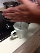 He removes the mug from the hot water and starts the foam process by hand.