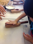 The kids, being eager, were patiently waiting their turn to get their hands on the dough ball's.